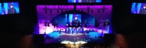 a mega church with multiple screens projecting the image of the speaker